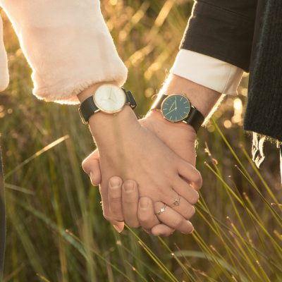 a couple holding hands in a field of tall grass
