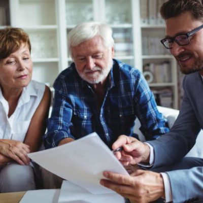elder couple meeting with financial advisor discusses retirement information