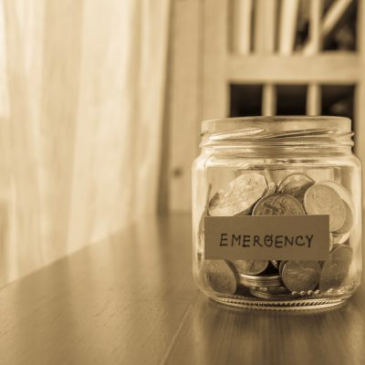 A savings money jar with world coins and emergency word on label or tag