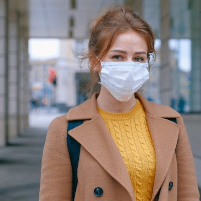 woman wearing a yellow sweater, tan jacket and a medical face mask outside in a city
