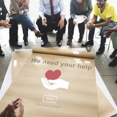 "group of people working on a banner that says ""we need your help"" for a charitable cause"