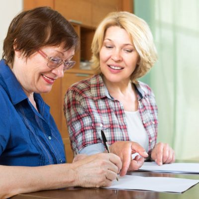 mature-woman-signing-paperwork-with-younger-woman