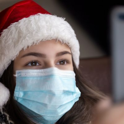 young-woman-in-face-mask-and-santa-hat-min