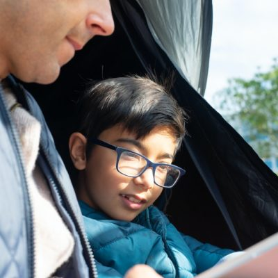 father-reading-to-son-while-camping